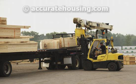 A roof truss being loaded by a forklift for shipping